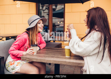 Two women chatting while having coffe in outdoor cafe. Happy friends using phone checking pictures. Girls hang out and having fun - Stock Photo