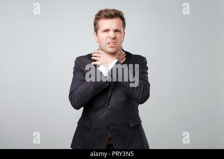 Young man in suit having asthma attack and can not breath suffering from respiration problems - Stock Photo