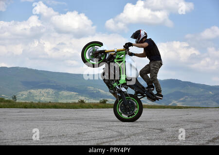 Stunt motorcyclist in action. Young man extreme freestyle biker training on abandoned wide empty airplane runway - Stock Photo