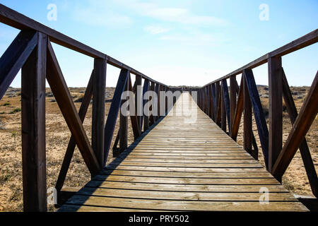 Wooden walkway over the sand dunes to the beach. Beach pathway in Huelva Beach, inside a nature reserve in Andalusia, Spain - Stock Photo
