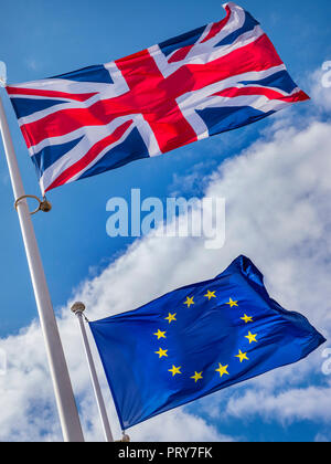 BREXIT FLAGS CONCEPT UK Union Jack Flag flying high above EU European Flag in a stiff breeze on a sunlit day with blue sky & flags divided by clouds - Stock Photo