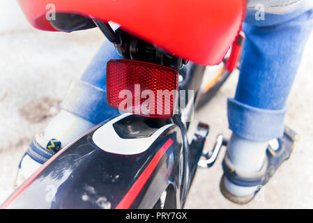 Child riding on bicycle. Close-up of rear reflector. - Stock Photo
