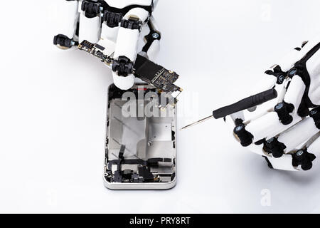 Robotic Hand Repairing Mobile Phone On White Background - Stock Photo
