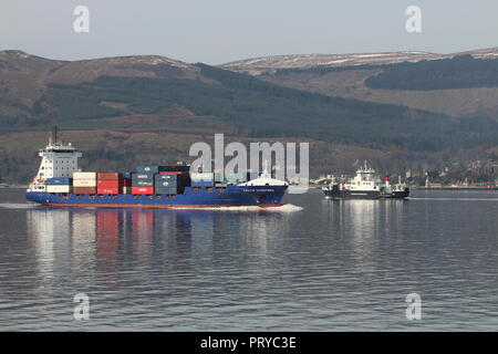 The container ship MS Kristin Schepers heading up the Firth of Clyde, passing the Caledonian MacBrayne car ferry Coruisk on an outbound journey. - Stock Photo