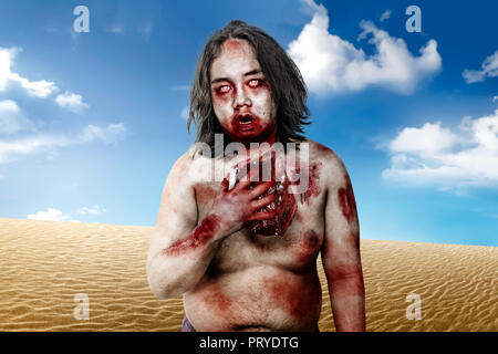 Spooky zombie man with bloody mouth holding raw meat on desert - Stock Photo
