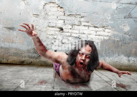 Creepy zombie man with bloody mouth crawling on old ruins place - Stock Photo