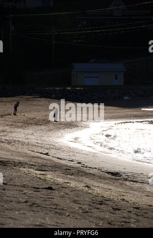 A old looking picture, 2 dark children silhouettes playing on the beach shore, with the bright water reflecting the sun, in Mont-Louis, Quebec, Canada - Stock Photo