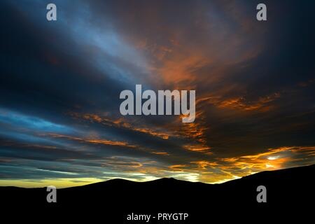 Dramatic sunset with rising storm clouds in front of mountain silhouette, Pali Aike National Park, Magallanes Province, Chile - Stock Photo