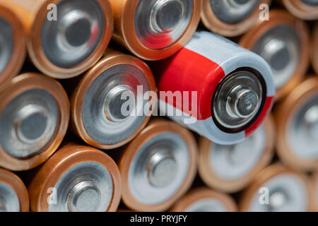 Stack of regular AA batteries with one sticking out by being different - rechargeable.