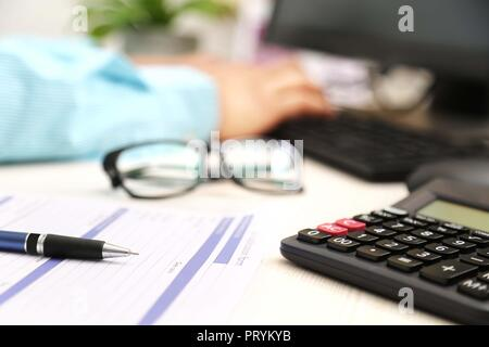 Picture of man hand is typing on keyboard. Picture of application form, pen, calculator and glasses. - Stock Photo