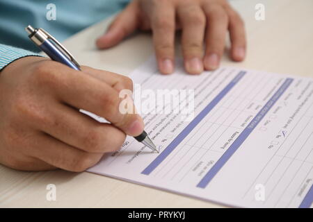 Picture of man hand is filling form with pen. - Stock Photo