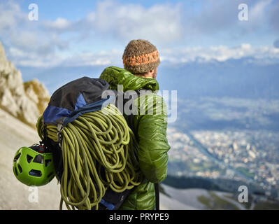 Austria, Innsbruck, Nordkette, man with rope and climbing equipment looking at view - Stock Photo