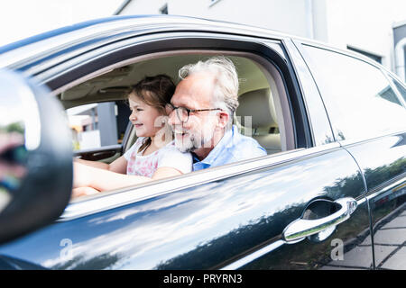 Little girl sitting on lap of grandfather, pretending to steer the car - Stock Photo