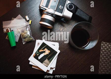Marihuana, cigarette lighter, polaroids and analog camera on wood - Stock Photo