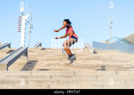 Young woman during workout on stairs, jumping - Stock Photo