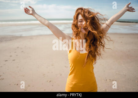 Redheaded woman, laughing happily in the wind - Stock Photo