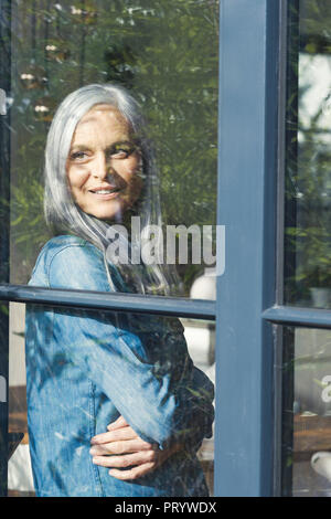 Senior woman looking out of window, smiling - Stock Photo