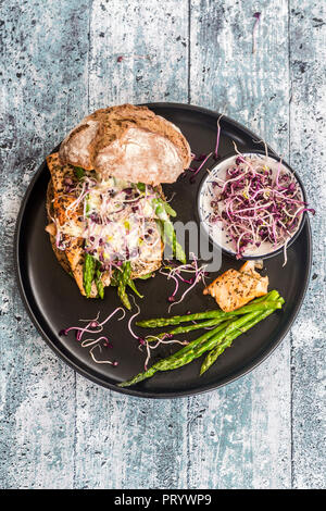 Salmon burger with green asparagus and red cress on plate - Stock Photo
