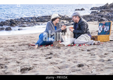 nice middle age caucasian couple happy have fun at the beach doing picnic together in outdoor sea leisure activity. family enjoying love and relations - Stock Photo