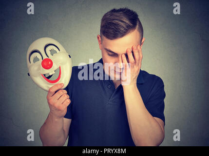 Young man holding colorful clown mask and looking upset being in depression and hiding feelings - Stock Photo