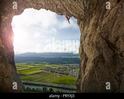 Austria, Innsbruck, Martinswand, man climbing in grotto - Stock Photo