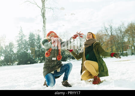 Two best friends having fun in the snow - Stock Photo