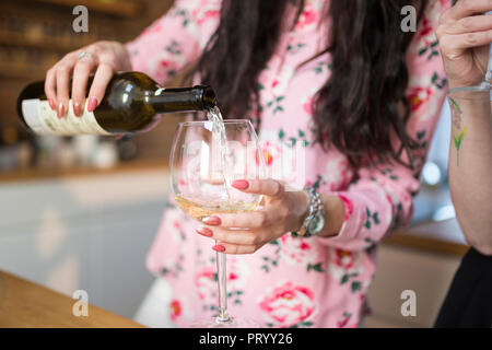 Close-up of woman pouring white wine into glass - Stock Photo