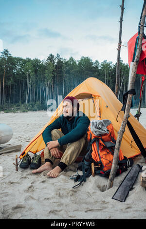 Backpacker sitting in front of his tent on the beach - Stock Photo