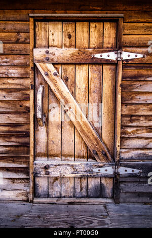 An old wooden door, leading to a wood building or a barn, with wooden handle. The building has been weathered for many years and shows significant wat - Stock Photo