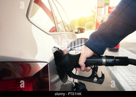 Car refueling on petrol station. Man pumping gasoline oil. This photo can be used for automotive industry or transportation concept - Stock Photo