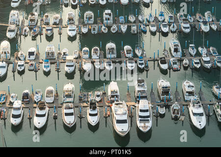 Yatch harbor marina pier and boat dock yatchs and vessels awaiting the open sea. Aerial drone view looking straight down above T-Head. - Stock Photo