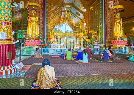 YANGON, MYANMAR - FEBRUARY 27, 2018: The prayer hall of Kyay Thone Pagoda, people pray at golden altar with many statues of Lord Buddha, on February 2 - Stock Photo