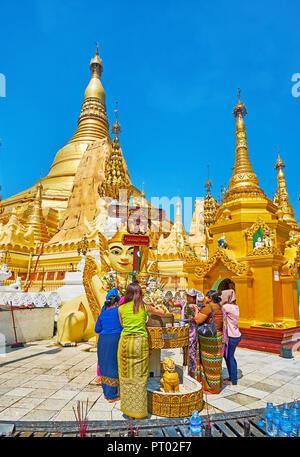 YANGON, MYANMAR - FEBRUARY 27, 2018: The Buddhist devotees perform the ritual of Buddha statue bathing in Shwedagon Pagoda with great golden stupas on - Stock Photo