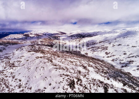 WHite snow slopes of the highest mountains in Australia under white clouds along Perisher valley with thick snow and ski resort sports tracks. - Stock Photo