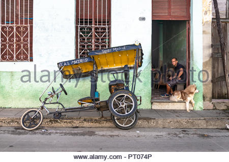 A 'bicitaxi' parked on a sidewalk. The land vehicle is leaned over the sidewalk no to interrupt traffic in the narrow urban street. - Stock Photo