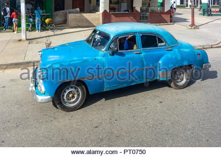 Vintage shabby American car driving on an urban street during the day. High angle view. Obsolete vehicles have become a tourist attraction in the Cari - Stock Photo