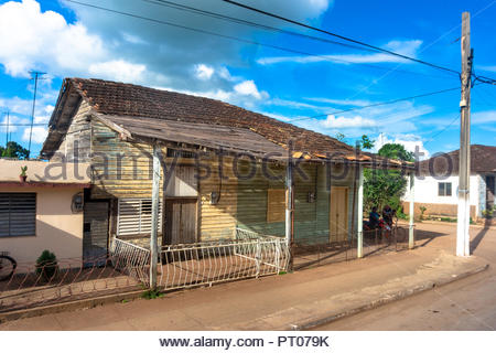 Old wooden house in a small town along the Central Road. The worn out house has missing tiles in the roof and weathered walls. - Stock Photo