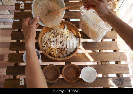 Preparation of granola, cooking process, healthy breakfast idea, vegan, dieting and detox concept. Oatmeal, dried fruits and berries, candied fruit, n - Stock Photo