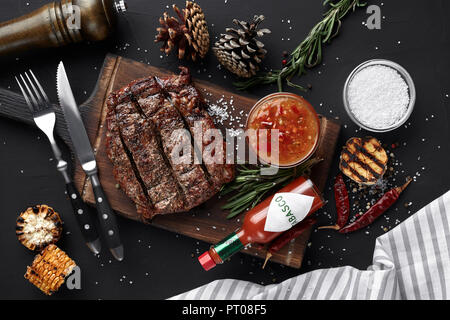 Medium rare grilled Steak Ribeye with corn and garlic on serving board block on black background. Top view. Still life. Flat lay - Stock Photo