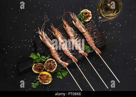 Grilled shrimp skewers. Seafood, shellfish. Shrimps Prawns skewers with herbs, garlic and lemon on black stone background, copy space. Barbecue shrimp - Stock Photo