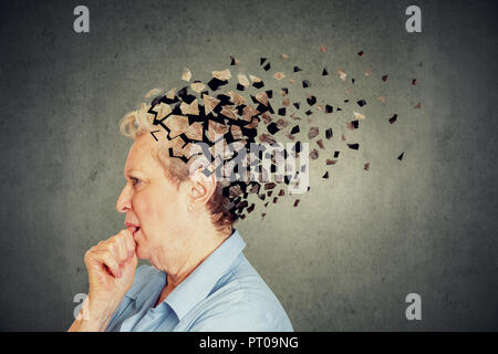 Memory loss due to dementia. Senior woman losing parts of head feeling confused as symbol of decreased mind function. - Stock Photo
