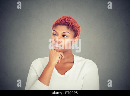 Woman thinking. Portrait of a serious beautiful young woman looking away - Stock Photo