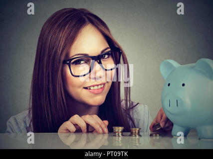 Young brunette in glasses at desk with blue piggy bank saving money looking at camera - Stock Photo