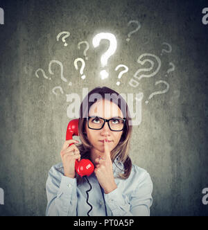 Misunderstanding and distant call. Confused worried woman talking on a phone has many questions isolated on gray background.