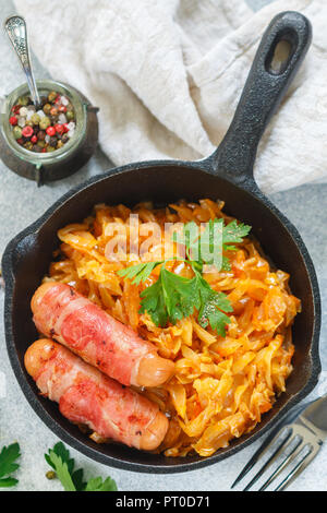 Stewed cabbage with carrots, onions and tomatoes and sausages in bacon with parsley and spices in a cast iron pan. Bigos. Delicious lunch. Selective f - Stock Photo