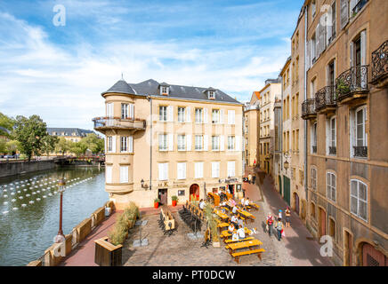 METZ, FRANCE - August 26, 2017: View on the riverside with beautiful old buildings and cafes in Metz city in Lorraine region of France - Stock Photo