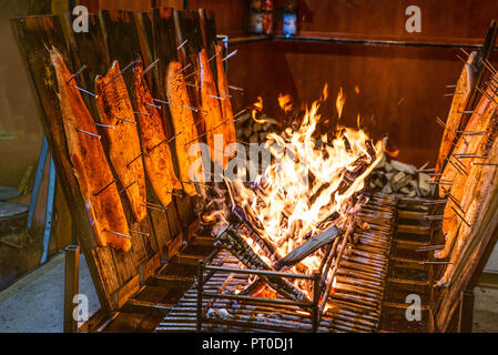 delicious flamed Salmon is smoked on open fire at Christmas market . - Stock Photo