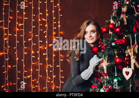 Beautiful woman in gray dress standing against decorated x-mas tree. - Stock Photo