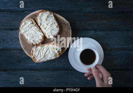 Healthy breakfast. Sandwiches with cream-cheese and coffee. Top view. Black wooden table. Cup of coffee in hand. - Stock Photo