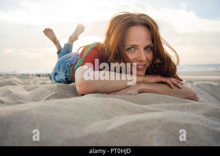 Redheaded woman lying in sand on the beach, smiling - Stock Photo